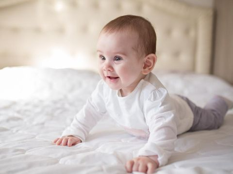 Cute little 10 months old baby lying on the bed and looking into the camera.
