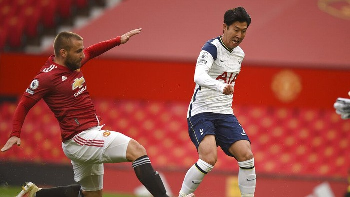 Tottenhams Son Heung-min, right, scores his sides second goal past Manchester Uniteds Luke Shaw, left, during the English Premier League soccer match between Manchester United and Tottenham Hotspur at Old Trafford in Manchester, England, Sunday, Oct. 4, 2020. (Oli Scarff/Pool via AP)