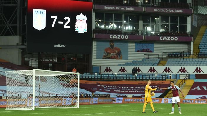 BIRMINGHAM, ENGLAND - OCTOBER 04: Adrian of Liverpool  shakes hands with Ollie Watkins of Aston Villa as the final score of 7-2 is seen on the big screen behind during the Premier League match between Aston Villa and Liverpool at Villa Park on October 04, 2020 in Birmingham, England. Sporting stadiums around the UK remain under strict restrictions due to the Coronavirus Pandemic as Government social distancing laws prohibit fans inside venues resulting in games being played behind closed doors. (Photo by Peter Powell - Pool/Getty Images)