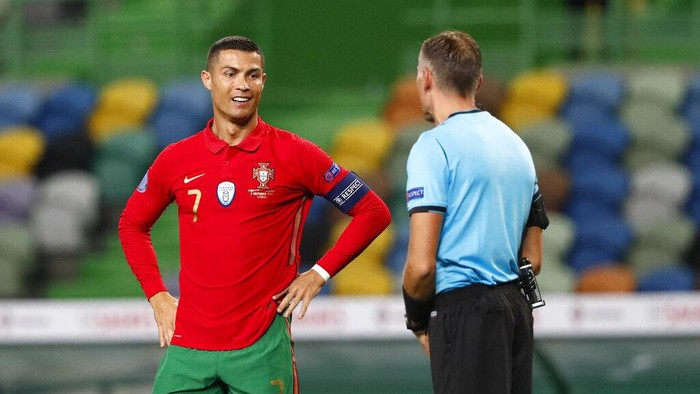Portugals Cristiano Ronaldo, left, speaks with referee Paolo Valeri during the international friendly soccer match between Portugal and Spain at the Jose Alvalade stadium in Lisbon, Wednesday, Oct. 7, 2020. (AP Photo/Armando Franca)
