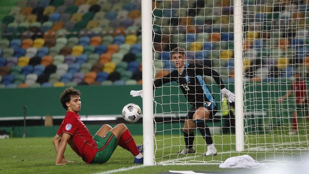 Portugal's Joao Felix, left, and Spain goalkeeper Kepa watch as the ball runs past the goal during the international friendly soccer match between Portugal and Spain at the Jose Alvalade stadium in Lisbon, Wednesday, Oct. 7, 2020. (AP Photo/Armando Franca)
