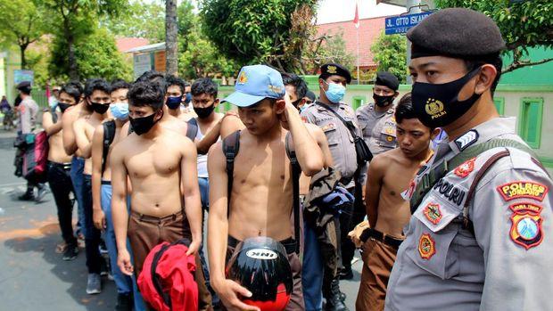 Pelajar SMK diamankan polisi saat hendak mengikuti demonstrasi menolak Omnibus Law UU Cipta Kerja di Gedung DPRD Kabupaten Jombang, Jawa Timur, Jumat (09/10/2020). Polres Jombang mengamankan 43 pelajar yang akan mengikuti aksi menolak UU Cipta Kerja. ANTARA FOTO/Syaiful Arif/pras.