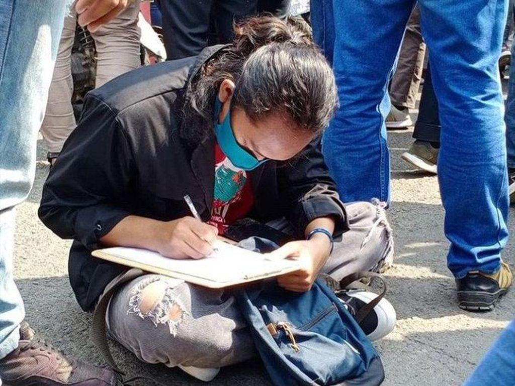 Viral, Mahasiswa Ini Sibuk Kerjakan Tugas Sambil Ikut Demo Omnibus Law