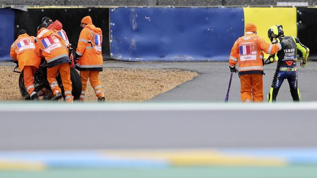 Italian rider Valentino Rossi of the Monster Energy Yamaha MotoGP, right, walks after falling down during the MotoGP race of the French Motorcycle Grand Prix at the Le Mans racetrack, in Le Mans, France, Sunday, Oct. 11, 2020. (AP Photo/David Vincent)