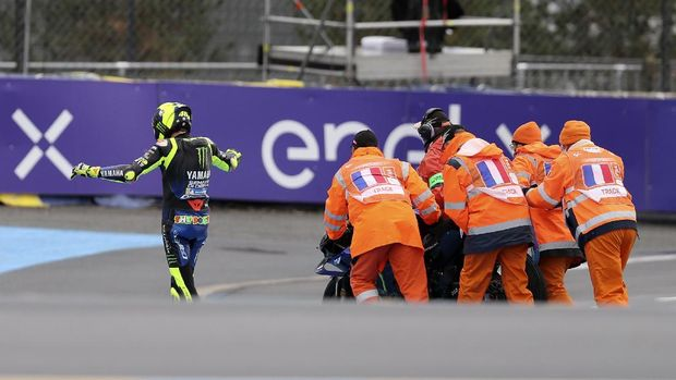 Marshals push Italian rider Valentino Rossi of the Monster Energy Yamaha MotoGP motorcycle after falls down during the MotoGP race of the French Motorcycle Grand Prix at the Le Mans racetrack, in Le Mans, France, Sunday, Oct. 11, 2020. (AP Photo/David Vincent)