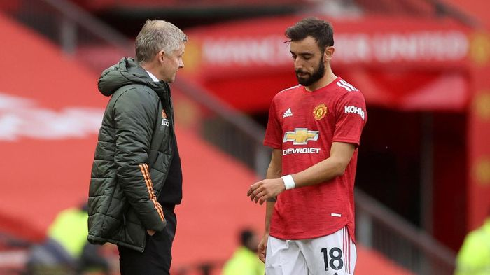 Manchester Uniteds Bruno Fernandes talks with Manchester Uniteds manager Ole Gunnar Solskjaer, center, as Tottenhams manager Jose Mourinho walks by during the English Premier League soccer match between Manchester United and Tottenham Hotspur at Old Trafford in Manchester, England, Sunday, Oct. 4, 2020. (Carl Recine/Pool via AP)