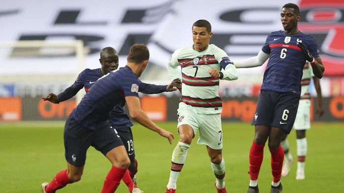 Portugals Cristiano Ronaldo, center, runs with the ball at Frances Benjamin Pavard, foreground, between Ngolo Kante and Paul Pogba, right, during the UEFA Nations League soccer match between France and Portugal at the Stade de France in Saint-Denis, north of Paris, France, Sunday, Oct. 11, 2020. (AP Photo/Thibault Camus)