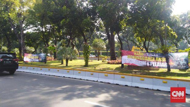 Spanduk tudingan KAMI di balik aksi mahasiswa dan pelajar terpasang di tepi Jalan Merdeka Barat, Jakarta Pusat, Senin (12/10).