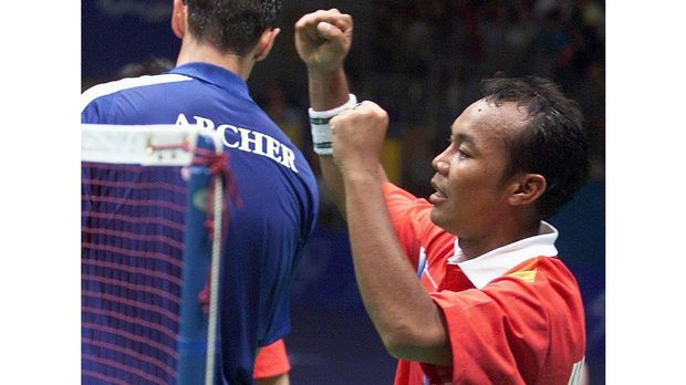 Indonesia's Tri Kusharyanto raises his arms in victory after he and partner Minarti Timur defeated Great Britain's Simon Archer and Joanne Goode 2-15, 17-15, 15-11 in the semifinal of the mixed doubles badminton at the Sydney Olympic Park 20 September 2000. The Indonesians will meet China's Zhang Jun and Gao Ling in the final. AFP PHOTO/Robyn BECK (Photo by ROBYN BECK / AFP)