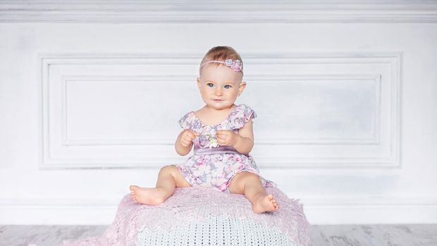 Little pretty girl with blue eyes sits on a padded stool