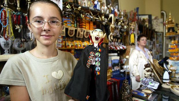 A shop vendor shows a Dracula doll in a souvenirs shop 26 July 2003, on the second day of the Medieval Art Festival in Sighisoara, some 300 km from Bucharest. Thousands of people came to the medieval fortress of Sighisoara for a three-day cultural event which gathers craftsmen, musicians and theater performers. AFP PHOTO DANIEL MIHAILESCU (Photo by DANIEL MIHAILESCU / AFP)