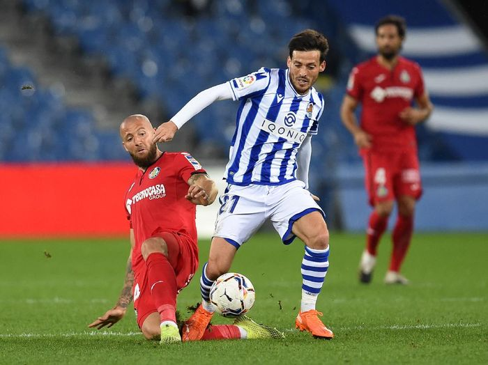 SAN SEBASTIAN, SPAIN - OCTOBER 03: David Silva of Real Sociedad is challenged by David Timor of Getafe CF during the La Liga Santader match between Real Sociedad and Getafe CF at Estadio Anoeta on October 03, 2020 in San Sebastian, Spain. Football Stadiums around Europe remain empty due to the Coronavirus Pandemic as Government social distancing laws prohibit fans inside venues resulting in fixtures being played behind closed doors. (Photo by Juan Manuel Serrano Arce/Getty Images)