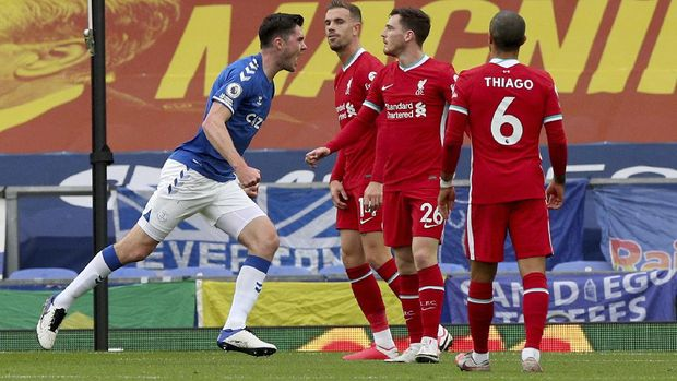 Everton's Michael Keane, left, celebrates scoring his side's first goal as Liverpool's Jordan Henderson, second left, reacts during the English Premier League soccer match between Everton and Liverpool at Goodison Park stadium, in Liverpool, England, Saturday, Oct. 17, 2020. (Peter Byrne/Pool via AP)