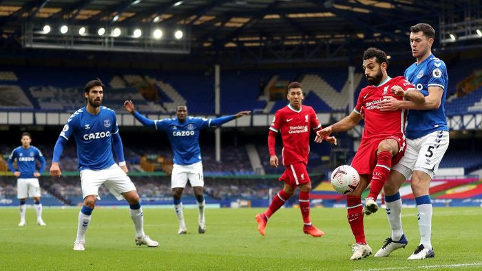 LIVERPOOL, ENGLAND - OCTOBER 17: Mohamed Salah of Liverpool holds off Michael Keane of Everton during the Premier League match between Everton and Liverpool at Goodison Park on October 17, 2020 in Liverpool, England. Sporting stadiums around the UK remain under strict restrictions due to the Coronavirus Pandemic as Government social distancing laws prohibit fans inside venues resulting in games being played behind closed doors. (Photo by Catherine Ivill/Getty Images)