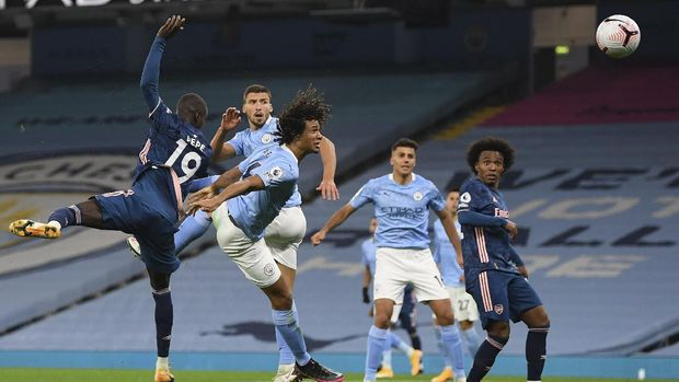 Arsenal's Nicolas Pepe, left, jumps for the ball with Manchester City's Nathan Ake, second left, during the English Premier League soccer match between Manchester City and Arsenal at the Etihad stadium in Manchester, England, Saturday, Oct. 17, 2020. (Michael Regan/Pool via AP)