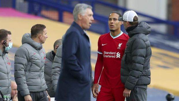 Liverpool's manager Jurgen Klopp, right, checks on Liverpool's Virgil van Dijk, second right, as he leaves the match with an injury during the English Premier League soccer match between Everton and Liverpool at Goodison Park stadium, in Liverpool, England, Saturday, Oct. 17, 2020. (Cath Ivill/Pool via AP)