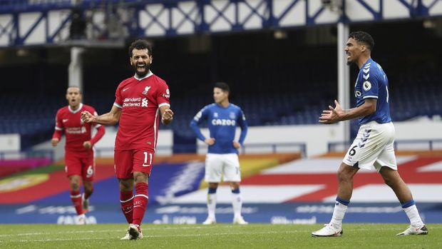 Liverpool's Mohamed Salah, 11, celebrates scoring his side's second goal as Everton's Allan, 6, reacts during the English Premier League soccer match between Everton and Liverpool at Goodison Park stadium, in Liverpool, England, Saturday, Oct. 17, 2020. (Cath Ivill/Pool via AP)