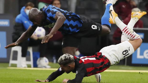 AC Milan's Theo Hernandez, bottom, and Inter Milan's Romelu Lukaku vie for the ball during the Serie A soccer match between Inter Milan and AC Milan at the San Siro Stadium, in Milan, Italy, Saturday, Oct. 17, 2020. (AP Photo/Antonio Calanni)