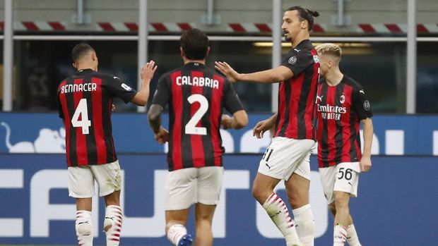 AC Milan's Zlatan Ibrahimovic celebrates with teammates keeping a safety distance after scoring his side's second goal during the Serie A soccer match between Inter Milan and AC Milan at the San Siro Stadium, in Milan, Italy, Saturday, Oct. 17, 2020. (AP Photo/Antonio Calanni)