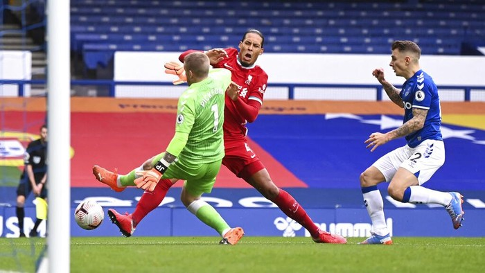 Liverpools Virgil van Dijk, centre, is tackled and injured by Evertons goalkeeper Jordan Pickford, left, causing him to leave the match injured during the English Premier League soccer match between Everton and Liverpool at Goodison Park stadium, in Liverpool, England, Saturday, Oct. 17, 2020. (Laurence Griffiths/Pool via AP)