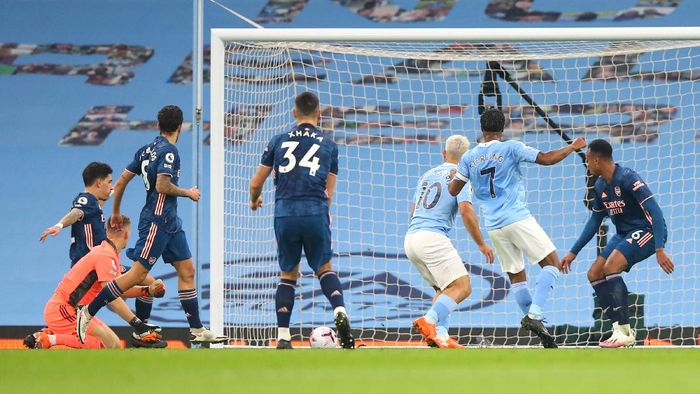 MANCHESTER, ENGLAND - OCTOBER 17: Raheem Sterling of Manchester City scores his sides first goal during the Premier League match between Manchester City and Arsenal at Etihad Stadium on October 17, 2020 in Manchester, England. Sporting stadiums around the UK remain under strict restrictions due to the Coronavirus Pandemic as Government social distancing laws prohibit fans inside venues resulting in games being played behind closed doors. (Photo by Alex Livesey/Getty Images)