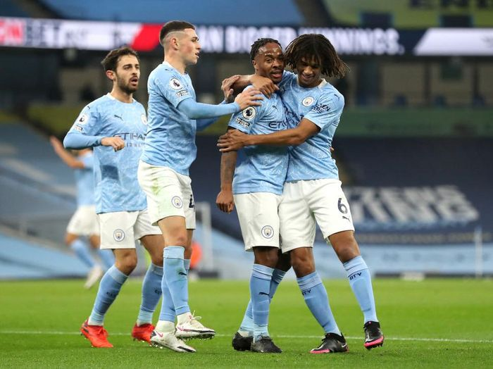 MANCHESTER, ENGLAND - OCTOBER 17: Raheem Sterling of Manchester City celebrates with teammates after scoring his teams first goal during the Premier League match between Manchester City and Arsenal at Etihad Stadium on October 17, 2020 in Manchester, England. Sporting stadiums around the UK remain under strict restrictions due to the Coronavirus Pandemic as Government social distancing laws prohibit fans inside venues resulting in games being played behind closed doors. (Photo by Martin Rickett - Pool/Getty Images)