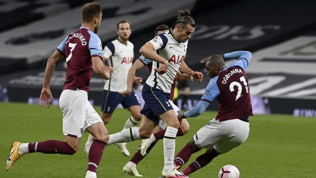 Tottenham's Gareth Bale, center, runs with the ball past West Ham's Angelo Ogbonna, right, during the English Premier League soccer match between Tottenham Hotspur and West Ham United at the Tottenham Hotspur Stadium in London, England, Sunday, Oct. 18, 2020. (Neill Hall/Pool via AP)