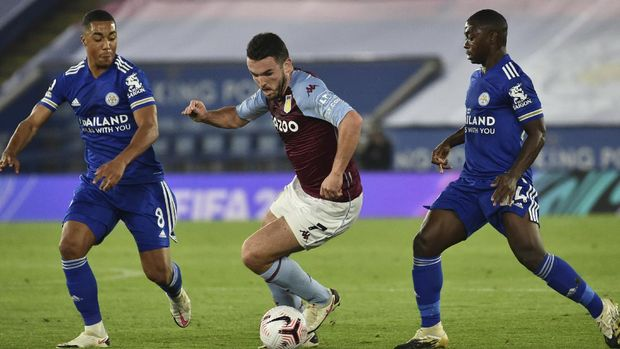 Aston Villa's John McGinn fights for the ball against Leicester's Youri Tielemans and Nampalys Mendy, right, during the English Premier League soccer match between Leicester City and Aston Villa at the King Power Stadium in Leicester, England, Sunday, Oct. 18, 2020. (AP Photo/Rui Vieira, Pool)