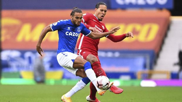 Everton's Dominic Calvert-Lewin, left, competes for the ball with Liverpool's Virgil van Dijk during the English Premier League soccer match between Everton and Liverpool at Goodison Park stadium, in Liverpool, England, Saturday, Oct. 17, 2020. (Laurence Griffiths/Pool via AP)