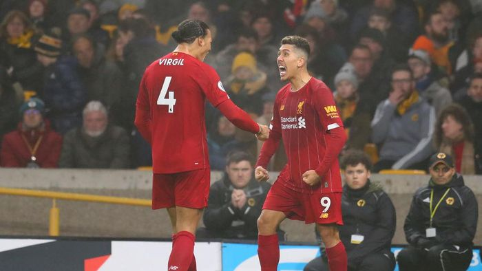WOLVERHAMPTON, ENGLAND - JANUARY 23:  Roberto Firmino of Liverpool celebrates with team-mate Virgil van Dijk after scoring their second goal during the Premier League match between Wolverhampton Wanderers and Liverpool FC at Molineux on January 23, 2020 in Wolverhampton, United Kingdom. (Photo by Catherine Ivill/Getty Images)