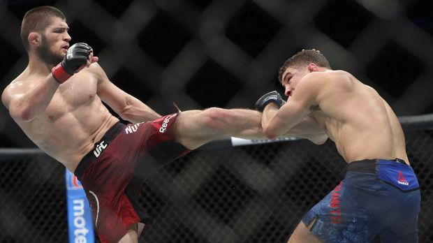 NEW YORK, NY - APRIL 07: Khabib Nurmagomedov (L) lands a kick on Al Iaquinta (R) during their UFC lightweight championship bout at UFC 223 at Barclays Center on April 7, 2018 in New York City.   Ed Mulholland/Getty Images/AFP