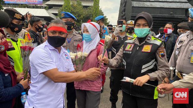 Massa buruh demo tola uu cipta kerja di Semarang bagikan bunga ke Polisi.