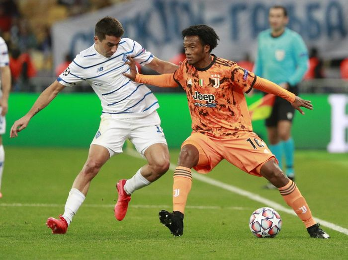 =Juventus Juan Cuadrado challenges for the ball with Dynamo Kyivs Artem Shabanov during the Champions League, group G, soccer match between Dynamo Kyiv and Juventus at the Olimpiyskiy Stadium in Kyiv, Ukraine, Tuesday, Oct. 20, 2020. (Valentyn Ogirenko/Pool via AP)