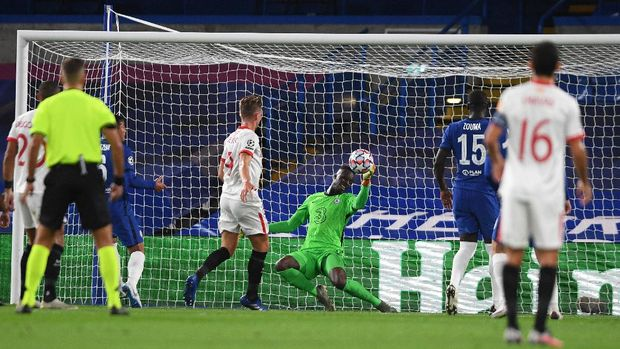 LONDON, ENGLAND - OCTOBER 20: Edouard Mendy of Chelsea makes a save during the UEFA Champions League Group E stage match between Chelsea FC and FC Sevilla at Stamford Bridge on October 20, 2020 in London, England. Sporting stadiums around the UK remain under strict restrictions due to the Coronavirus Pandemic as Government social distancing laws prohibit fans inside venues resulting in games being played behind closed doors. (Photo by Mike Hewitt/Getty Images)