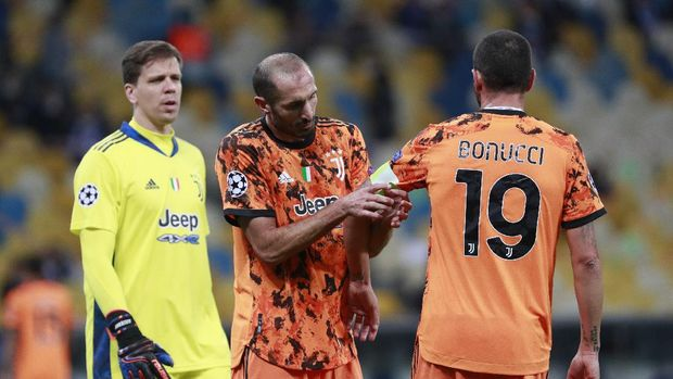 Juventus' Giorgio Chiellini, center, adjusts the captain's hand band on Juventus' Leonardo Bonucci during the Champions League, group G, soccer match between Dynamo Kyiv and Juventus at the Olimpiyskiy Stadium in Kyiv, Ukraine, Tuesday, Oct. 20, 2020. (Valentyn Ogirenko/Pool via AP)