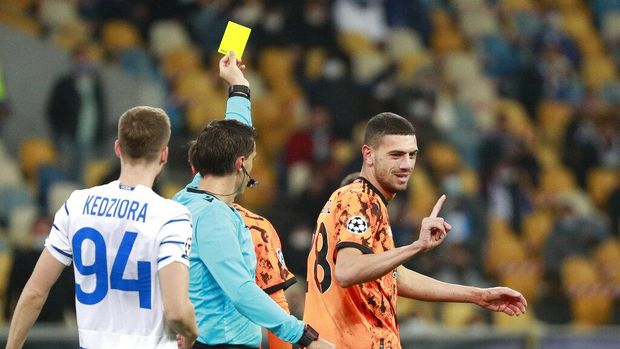 Juventus' Merih Demiral gestures as the referee shows him a yellow card after a foul on Dynamo Kyiv's Vladyslav Supriaha during the Champions League, group G, soccer match between Dynamo Kyiv and Juventus at the Olimpiyskiy Stadium in Kyiv, Ukraine, Tuesday, Oct. 20, 2020. (Valentyn Ogirenko/Pool via AP)