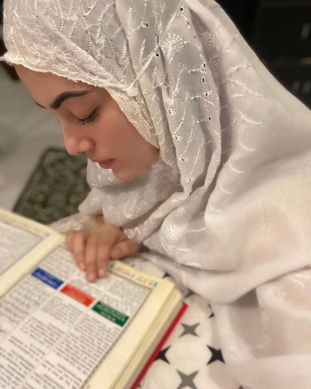 Potret Sana Khan saat membaca ayat suci Al-Qur'an.