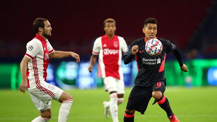 AMSTERDAM, NETHERLANDS - OCTOBER 21: Roberto Firminho of Liverpool runs with the ball under pressure from Daley Blind of Ajax during the UEFA Champions League Group D stage match between Ajax Amsterdam and Liverpool FC at Johan Cruijff Arena on October 21, 2020 in Amsterdam, Netherlands. (Photo by Dean Mouhtaropoulos/Getty Images)