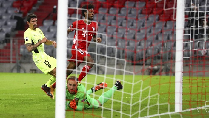 Bayern Munichs Kingsley Coman, centre, kicks the ball past Atletico Madrids Stefan Savic, left, and goalkeeper Jan Oblak to score his teams first goal during the Champions League Group A soccer match between Bayern Munich and Atletico Madrid at the Allianz Arena in Munich, Germany, Wednesday, Oct. 21, 2020. (AP Photo/Matthias Schrader,Pool)