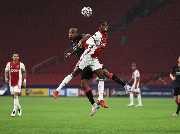Liverpools Brazilian midfielder Fabinho (L) jumps for the ball with Ajaxs Dutch midfielder Ryan Gravenberch  during the UEFA Champions League Group D first-leg football match between Ajax Amsterdam and Liverpool FC at the Johan Cruijff Arena in Amsterdam on October 21, 2020. (Photo by KENZO TRIBOUILLARD / AFP)