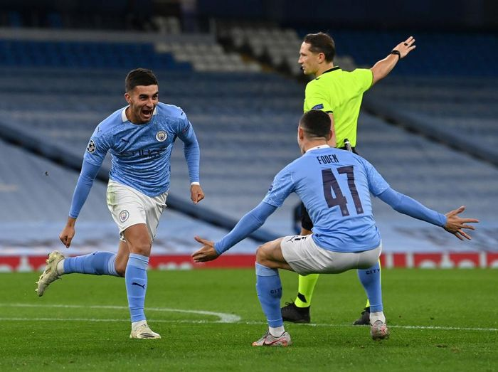 MANCHESTER, ENGLAND - OCTOBER 21: Ferran Torres of Manchester City celebrates with teammate Phil Foden after scoring his sides third goal during the UEFA Champions League Group C stage match between Manchester City and FC Porto at Etihad Stadium on October 21, 2020 in Manchester, England. Sporting stadiums around the UK remain under strict restrictions due to the Coronavirus Pandemic as Government social distancing laws prohibit fans inside venues resulting in games being played behind closed doors. (Photo by Paul Ellis - Pool/Getty Images)