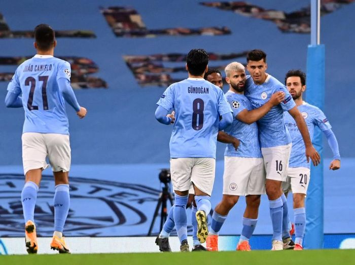MANCHESTER, ENGLAND - OCTOBER 21: Sergio Aguero of Manchester City celebrates with teammates after scoring his sides first goal during the UEFA Champions League Group C stage match between Manchester City and FC Porto at Etihad Stadium on October 21, 2020 in Manchester, England. Sporting stadiums around the UK remain under strict restrictions due to the Coronavirus Pandemic as Government social distancing laws prohibit fans inside venues resulting in games being played behind closed doors. (Photo by Laurence Griffiths/Getty Images)