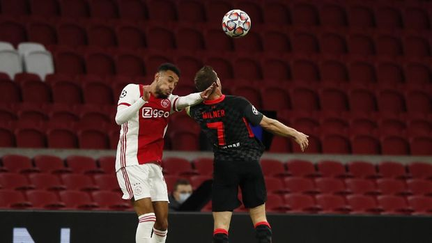 Ajax's Noussair Mazraoui, left and Liverpool's James Milner, right fight for the ball during the group D Champions League soccer match between Ajax and Liverpool at the Johan Cruyff ArenA in Amsterdam, Netherlands, Wednesday, Oct. 21, 2020. (AP Photo/Peter Dejong)