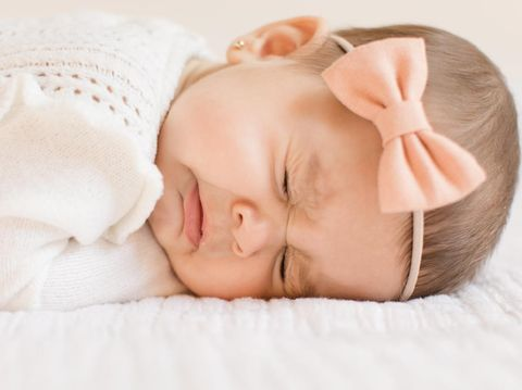 A 6-month old baby girl wearing a white outfit and a peach-colored bow laying on a white blanket, sneezing.