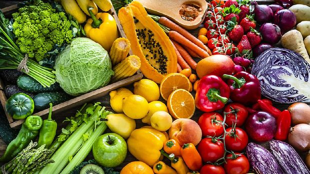 High angle view of a large assortment of healthy fresh rainbow colored organic fruits and vegetables. The composition includes cabbage, carrots, onion, tomatoes, raw potato, avocado, asparagus, eggplant, celery, cucumber, broccoli, squash, lettuce, spinach, lemon, apples, pear, strawberries, papaya, mango, banana, grape fruit, oranges, kiwi fruit among others. The composition is at the left of an horizontal frame leaving useful copy space for text and/or logo at the right. High resolution 42Mp studio digital capture taken with SONY A7rII and Zeiss Batis 40mm F2.0 CF lens
