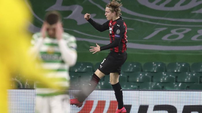 AC Milans Jens Petter Hauge jumps to celebrate after scoring his sides third goal during the Europa League Group H first leg soccer match between Celtic and AC Milan at the Celtic Park stadium in Glasgow, Scotland, Thursday, Oct. 22, 2020. AC Milan won the match 3-1. (Jane Barlow/Pool via AP)