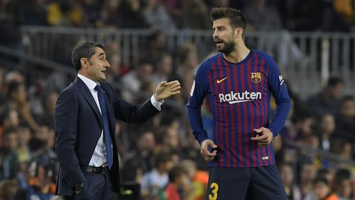 Barcelonas Spanish coach Ernesto Valverde (L) speaks to Barcelonas Spanish defender Gerard Pique during the Spanish league football match FC Barcelona against Sevilla FC at the Camp Nou stadium in Barcelona on October 20, 2018. (Photo by LLUIS GENE / AFP)