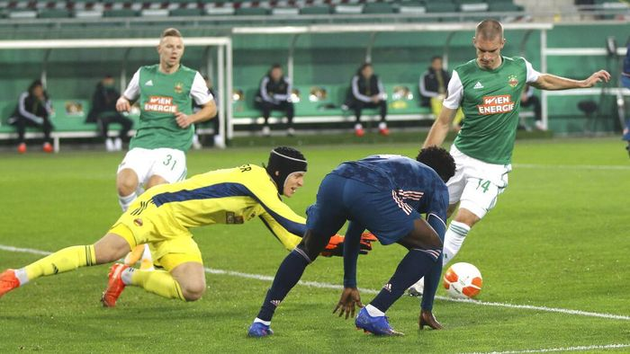 Rapid Wiens goalkeeper Richard Strebinger, left, and his teammate Srdan Grahovac, right, fights for the ball with Arsenals Bukayo Saka during the Europa League group B soccer match between SK Rapid Wien and FC Arsenal at the Alianz Stadium in Vienna, Austria, Thursday, Oct. 22, 2020. (AP Photo/Ronald Zak)
