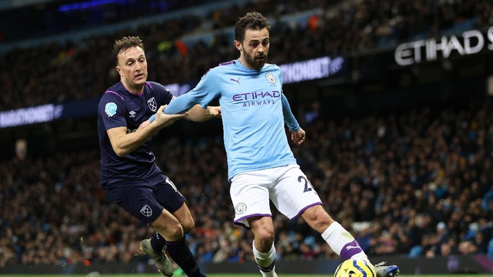 MANCHESTER, ENGLAND - FEBRUARY 19: Bernardo Silva of Manchester City and Mark Noble of West Ham United in action during the Premier League match between Manchester City and West Ham United at Etihad Stadium on February 19, 2020 in Manchester, United Kingdom. (Photo by Clive Brunskill/Getty Images)