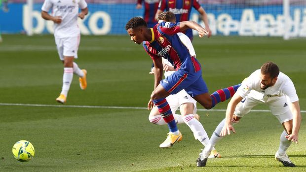 Barcelona's Ansu Fati fights for the ball against Real Madrid's Nacho during the Spanish La Liga soccer match between FC Barcelona and Real Madrid at the Camp Nou stadium in Barcelona, Spain, Saturday, Oct. 24, 2020. (AP Photo/Joan Monfort)